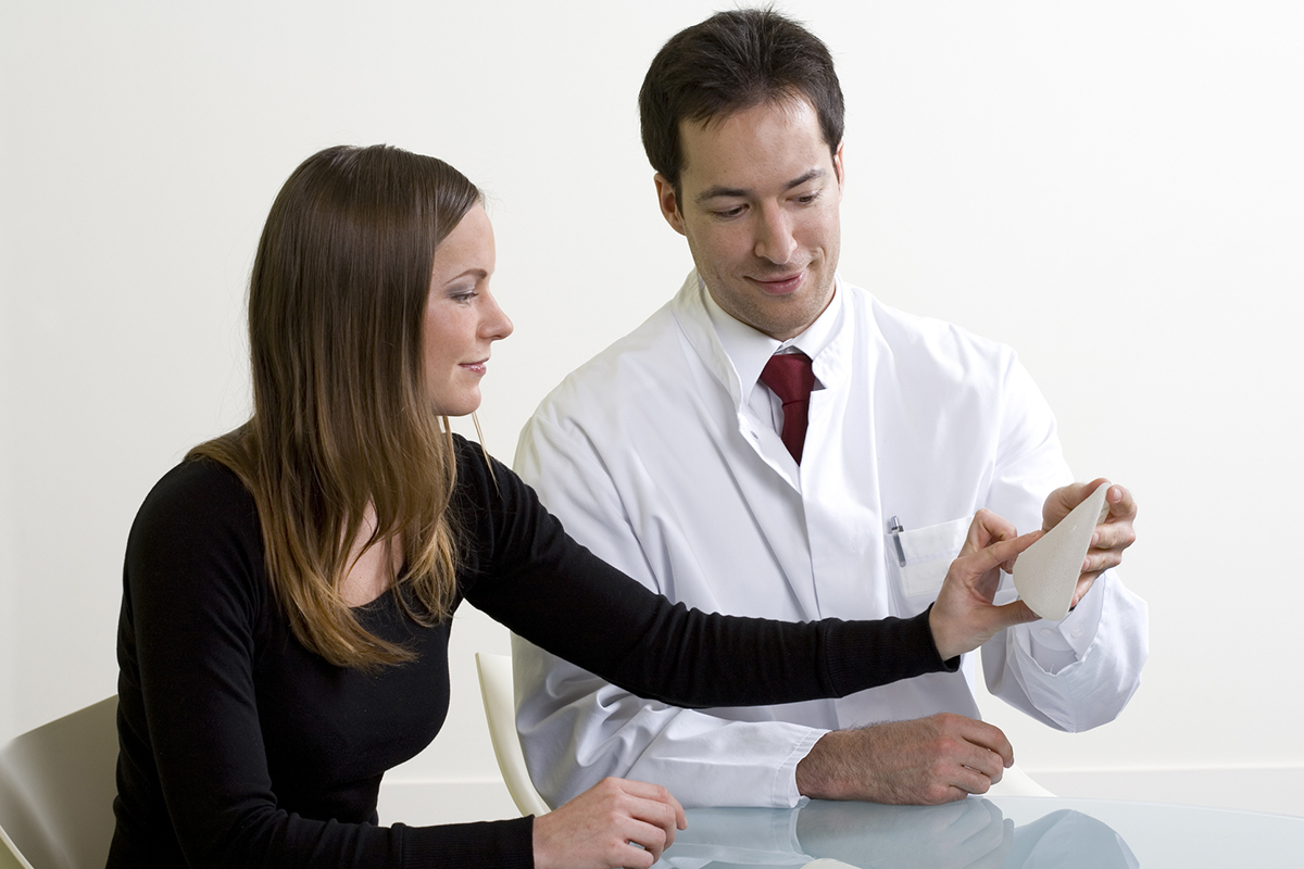 Physician showing a breast implant to a patient
