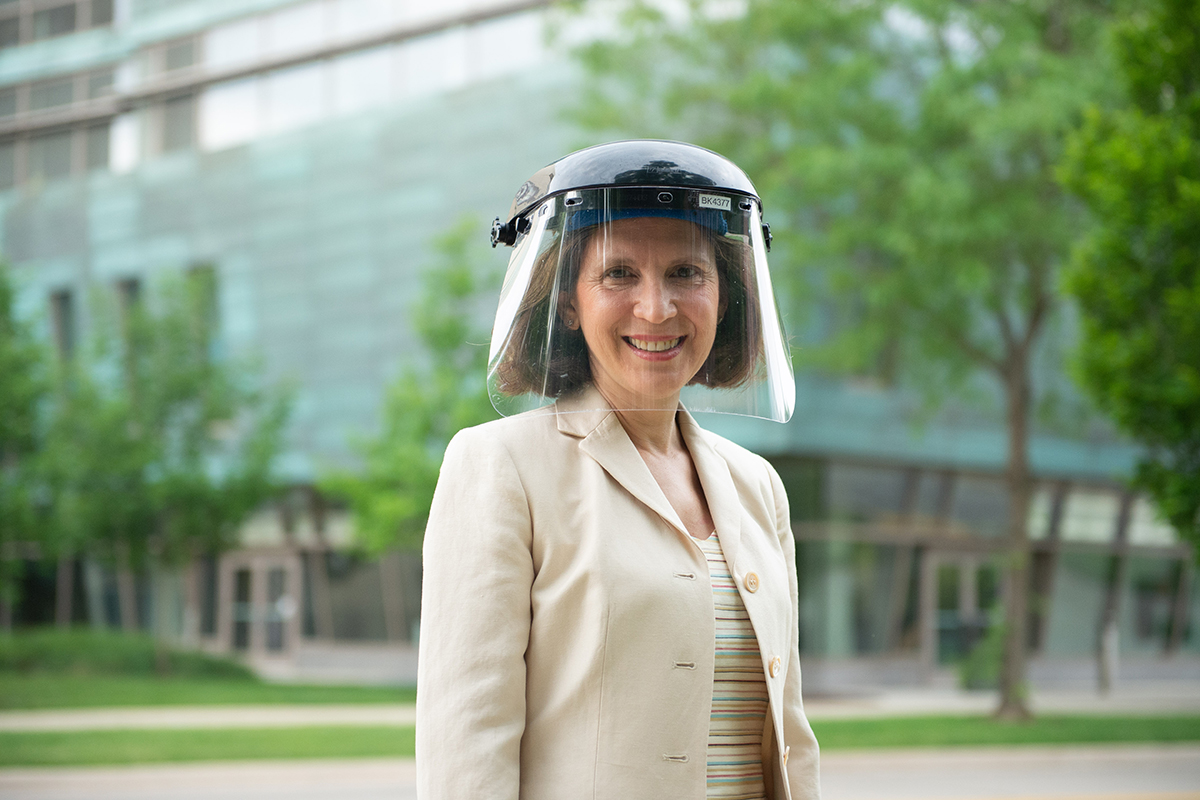 Dilek Ince, MD, stands on the UI Carver College of Medicine campus wearing a face shield