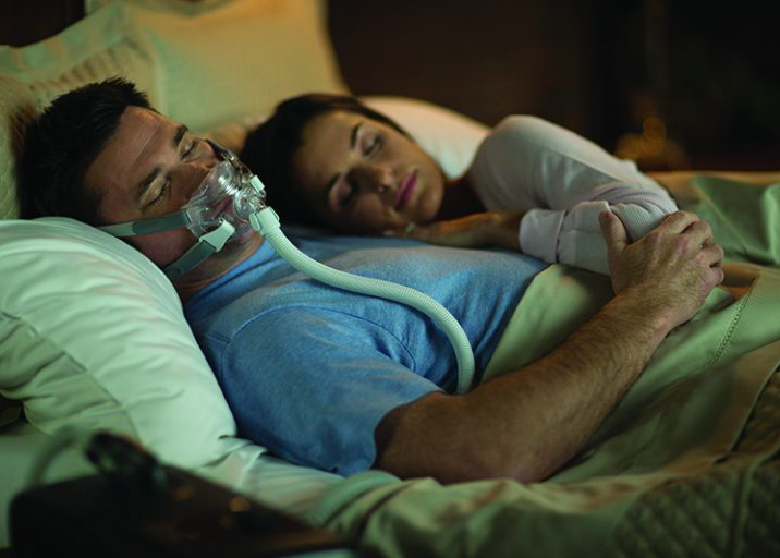 Sleeping in bed with CPAP mask