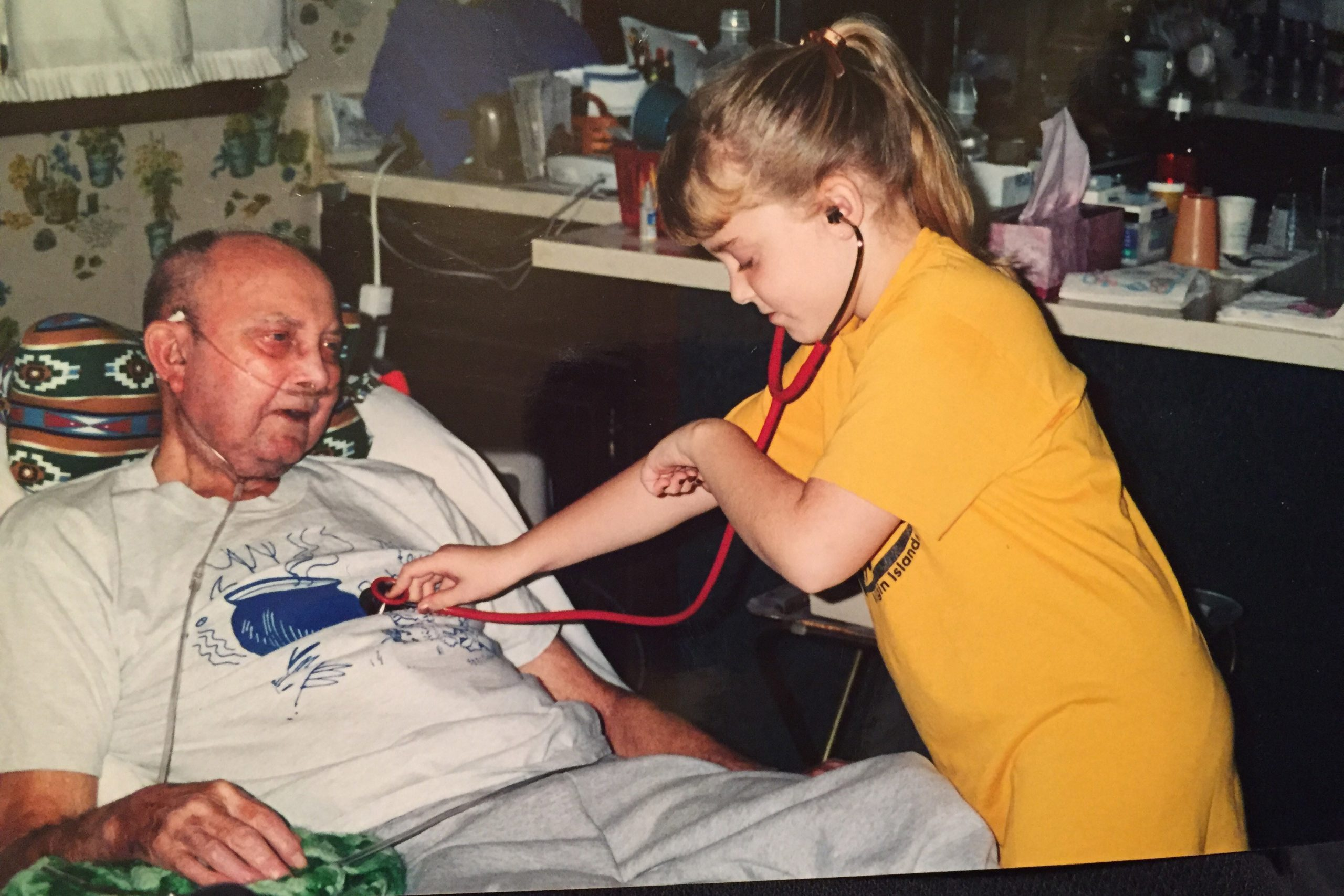 Marisa Weaver as a child, listening to her grandfather's heart with a stethoscope
