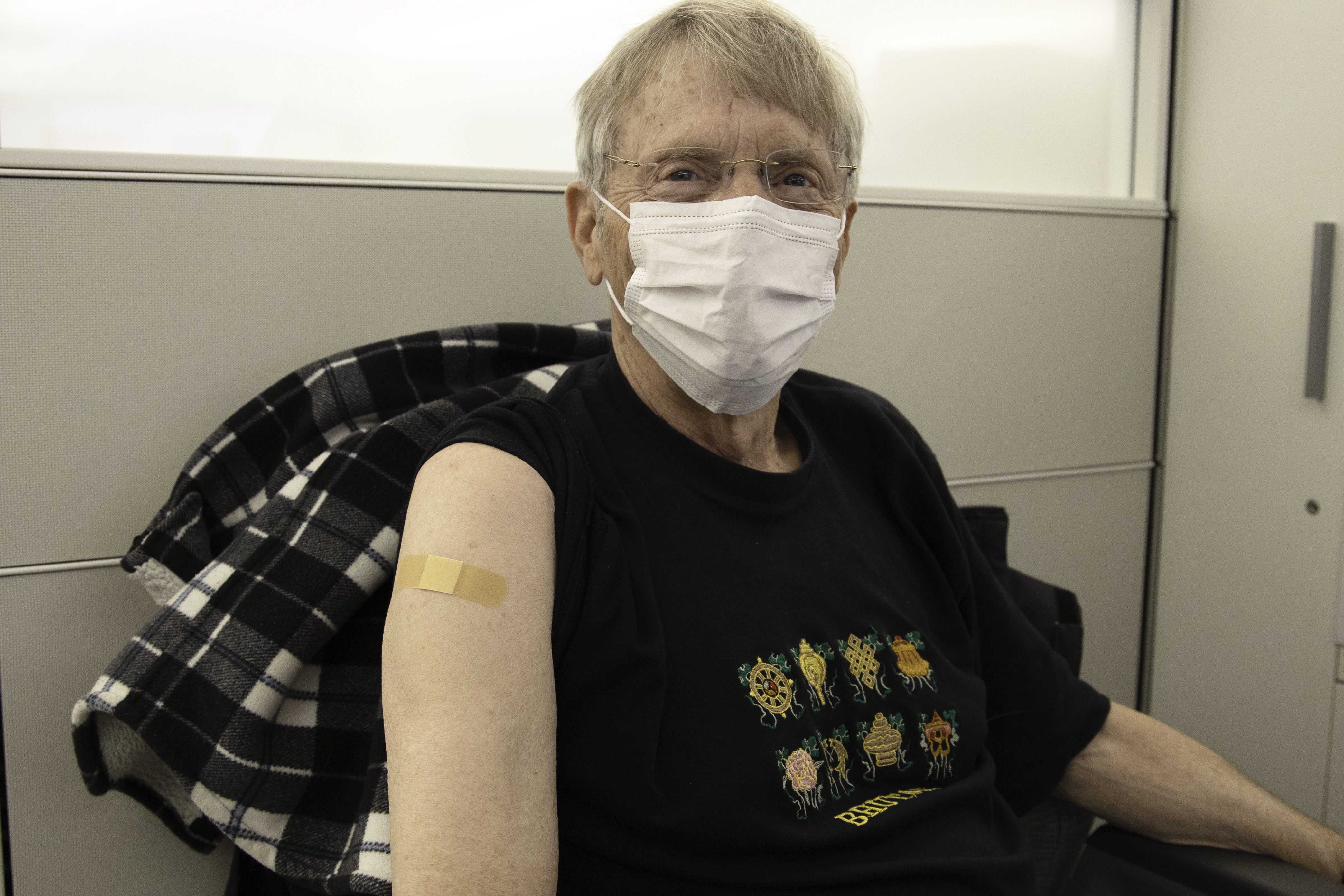 A patient poses after receiving the first dose of a COVID-19 vaccine