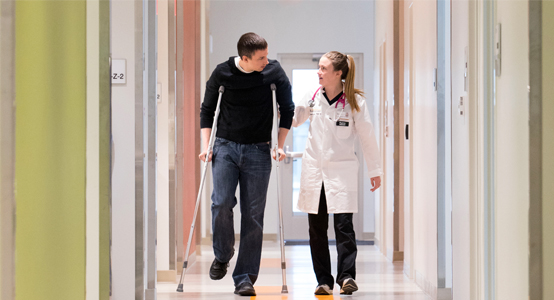 UI Health Care provider Tiffany Sorensen walks with a patient down a hallway at the Scott Blvd. Urgent Care location