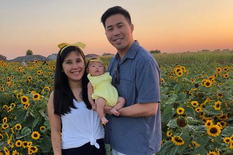Michael and Tina Lung hold their daughter, Makayla Lily Lung, outside by a field of sunflowers