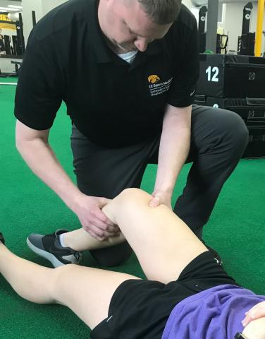 Athletic trainer, Johnnie James, works with a student at Regina High School