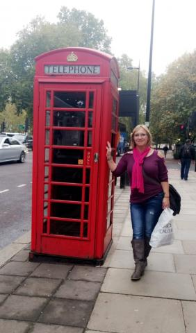Lynnita Truesdell stands next to a telephone booth while traveling abroad