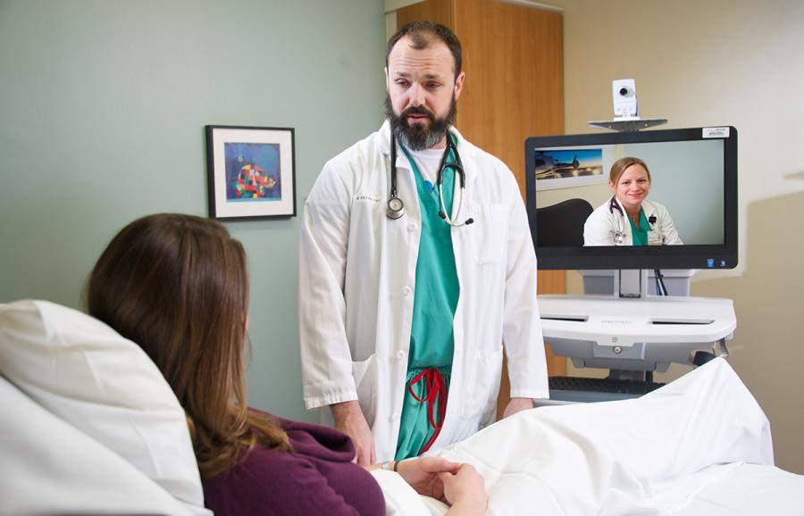 Doctor with patient and hospitalist observing through computer