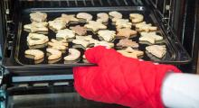 oven mitt holding pan of cookies