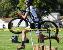 Cyclo-cross competitor carrying bike over obstacle