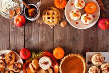 A table full of delicious holiday desserts including pumpkin pie and cupcakes