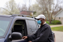 Black man wearing a mask opens his car door