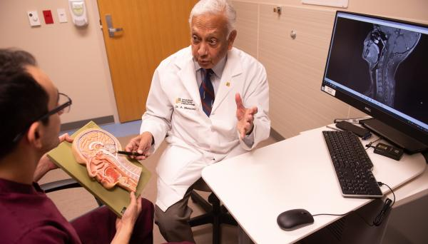 Neurosurgery resident interacts with provider at UI Health Care