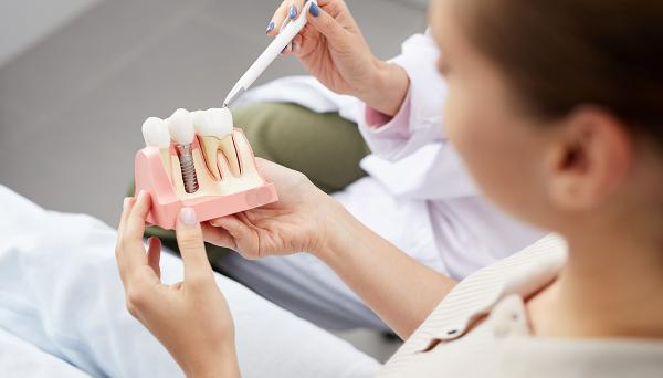 Dentist and patient look at a tooth model
