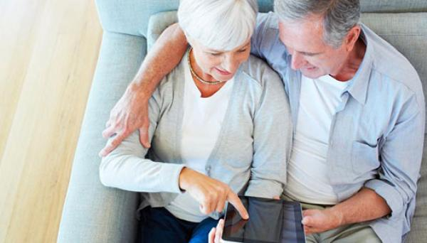 Senior couple looking at a tablet on their couch