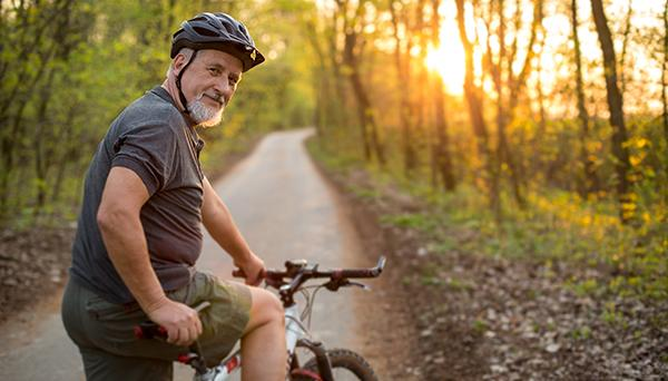 Man riding his bicycle on a path in the woods
