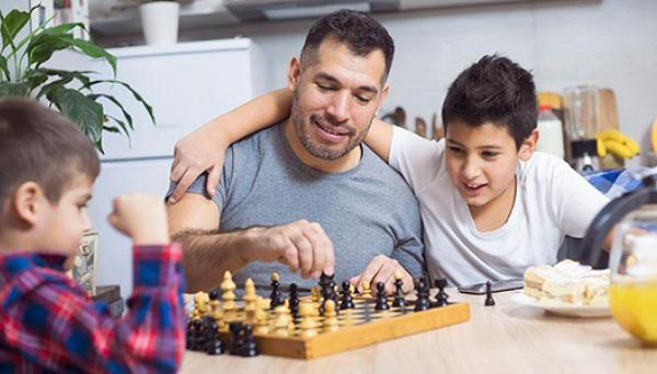 Father and sons playing chess