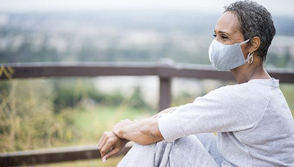 Woman relaxing outside wearing a face mask