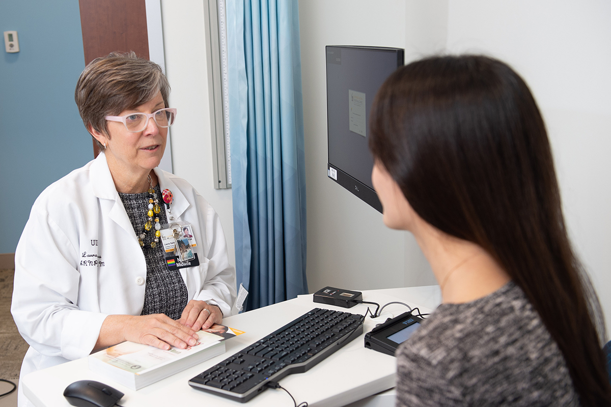 Laura Dellos, ARNP, CNM, speaks with a patient
